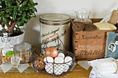 Wire basket of eggs and onions and other old kitchen utensils