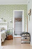Blick vom Schlafzimmer mit grün gemusterter Tapete ins Nebenzimmer