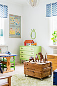Toys on old wooden crate with castors in vintage-style child's bedroom