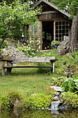 Rustic wooden bench with view of garden pond and orangery in background