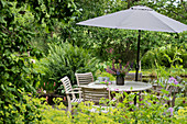 Round table, chairs and parasol on terrace in densely planted garden