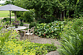 Paved path leading to round table, chairs and parasol on terrace in densely planted garden