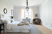Elegantes Schlafzimmer mit Wandverkleidung und Stuckdecke