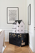 Dolls' house on old black trunk in corner