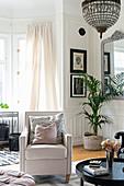 Heller Sessel im eleganten Wohnzimmer mit Kassettenwänden