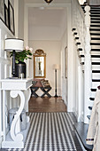 Staircase and console table in elegant foyer