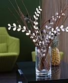 Blätterzweig aus Metall und Zweige in einer Glasvase
