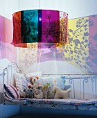 Lamp casting colourful patterns on walls above metal bed in child's bedroom