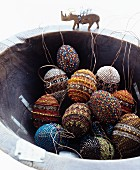 Easter eggs decorated with beads in rustic bowl with rhino figurine on rim