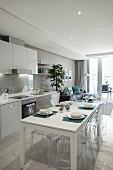 Einbauküche und weisser, gedeckter Esstisch in offenem Wohnraum