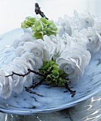 White china flowers, green flowers and twig in dish