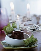 Candle in chocolate desert decorated with green hazelnuts