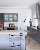 Kitchen counter and bar stools in fitted country-house-style kitchen