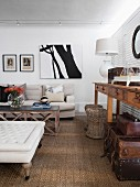 Sisal rug, wicker stools and pale sofa in country-house-style living area