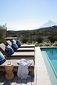 Upholstered sun loungers next to pool with view of summery landscape