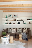 White shelves on wall above sofa with scatter cushions in comfortable lounge area