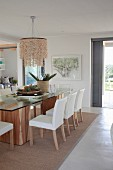 Dining table with glass top and white upholstered chairs in front of terrace door