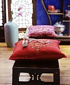 Embroidered cushions on wooden bench