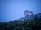 Modern cubist house protruding out from hilltop in the fog