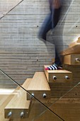 Person walking down floating staircase with glass balustrade