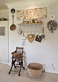 Vintage-style arrangement on wall with motto above vintage high chair and raffia shopping basket on tiled floor
