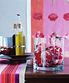 Radicchio and rose petals in glass bowl and olive oil on wooden table