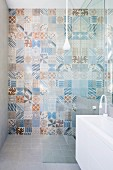 Various wall tiles with retro patterns in pastel blue and brown shades in shower area