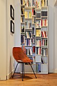 White bookcase and retro chair in reading corner in period apartment