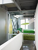 View from hallway with white balustrade wall to glass sliding door and suspended bed