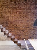 Self-supporting sheet-steel staircase against brick wall