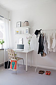Desk and coat racks in simple room in grey and white