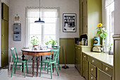 Old table and chairs in retro kitchen with olive-green cabinets