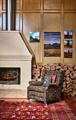 Upholstered armchairs in front of wood storage and fireplace on cassette paneling