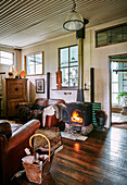 Fireplace with fire and vintage leather furniture in a converted stable