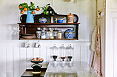 Antique wall shelf in the kitchen with porcelain jars, storage glasses and mandarin branch
