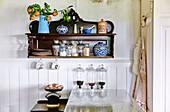 Antik Wandregal mit Porzellangefässen, Aufbewahrungsgläsern und Mandarinenzweig in der Küche