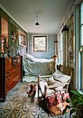Rustikaler Stuhl, Antik Kommode und Bett im Schlafzimmer in umgebautem Stall