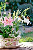 Pink lily in flower-patterned pot