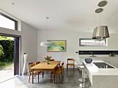 Offene Küche mit Essplatz vor geöffneter Terrassenschiebetür