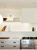 White wall-mounted shelves, indirect lighting and gas hob in kitchen