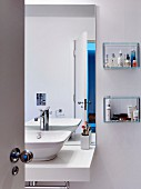 Washstand, wall-mounted mirror and small glass shelves in bathroom
