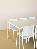 White table with glass top and designer chairs in front of empty wall