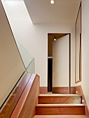 Wooden staircase leading to hidden door with wooden skirting board
