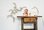 Artistic floral paper decoration on wall next to antique wooden table and retro lamp