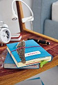 A notebook with blue felt cover and a quill pen on a bedside table