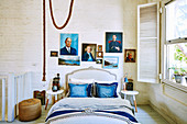 Double bed with blue pillows and portrait painting on white painted brick wall