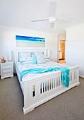 Weisses Doppelbett mit Holzgestell in hellem Schlafzimmer