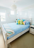 Double bed with colorful pillows in bright guest room
