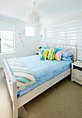 Doppelbett mit bunten Kissen in hellem Gästezimmer