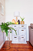 Houseplant on plant stand in front of limed chest of drawers